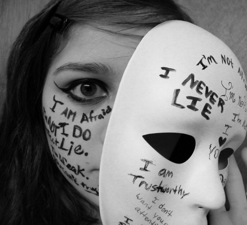 woman with writing on her face taking off a mask